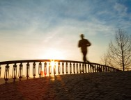 jogger running in sunrise over bridge with clouds