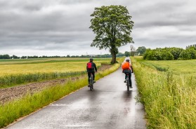 Bicycling on rainy weather near green fields outdoor