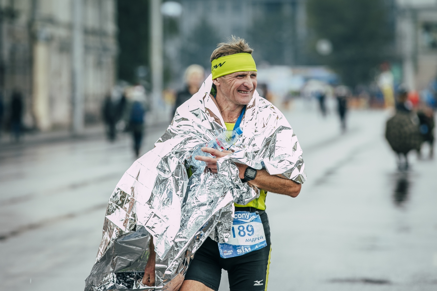 athlete runner middle-aged after the finish put on aluminum foil
