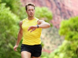 Runner looking at heart rate monitor smartwatch while running. M