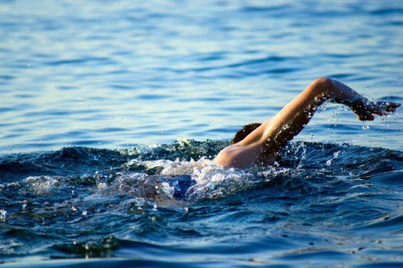 swimming man in ocean water