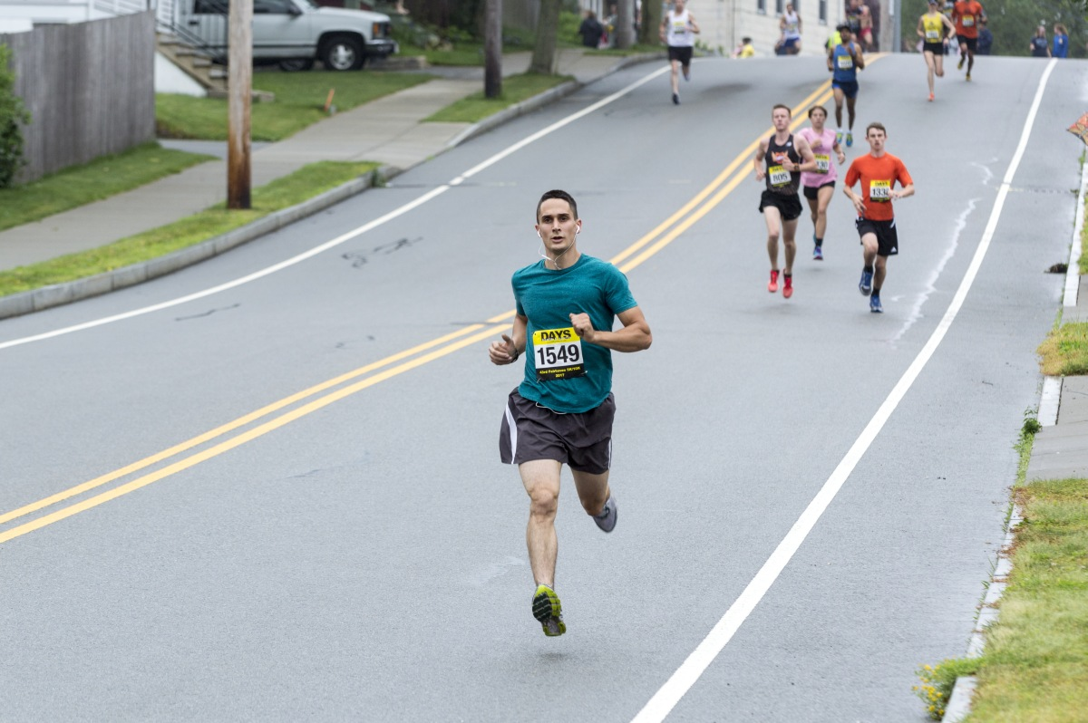 Fairhaven Massachusetts USA - June 18 2017: Runner in the air on downhill section of Fairhaven Road Race