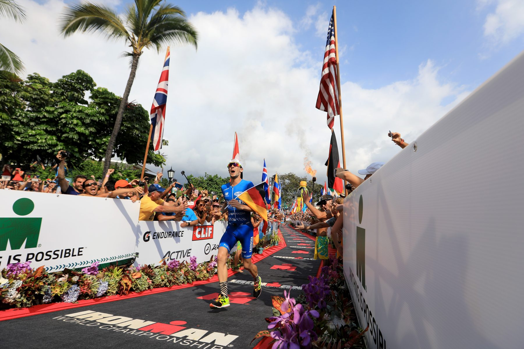 KAILUA KONA, HI - OCTOBER 14: Patrick Lange of Germany celebrates before crossing the finish line to win the IRONMAN World Championship and setting a course record of 8:01.39 beating Craig Alexander's 2011 record of 8:03.56 on October 14, 2017 in Kailua Kona, Hawaii. (Photo by Sean M. Haffey/Getty Images for IRONMAN)